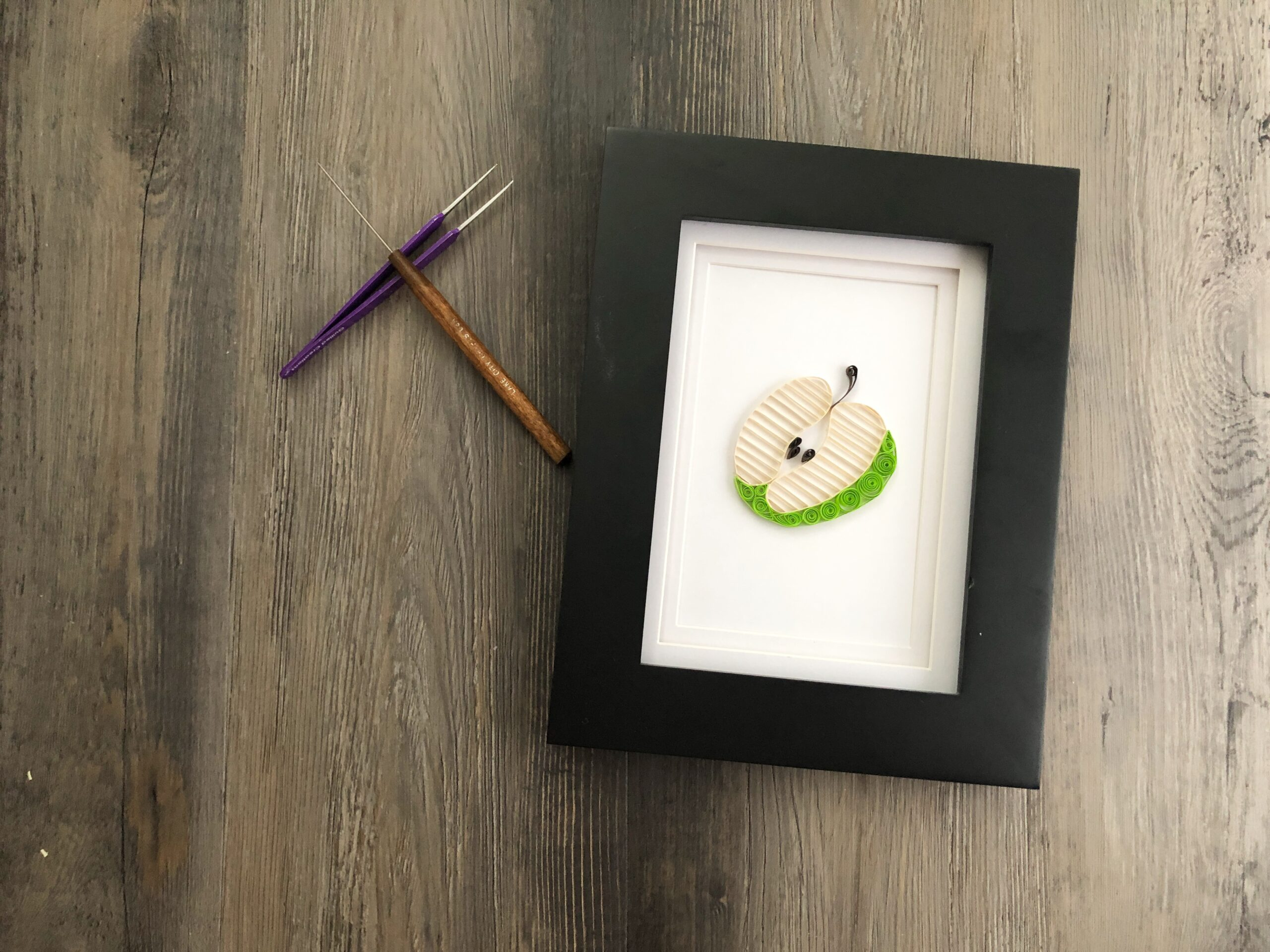 quilling paper apple in frame with quilling tools
